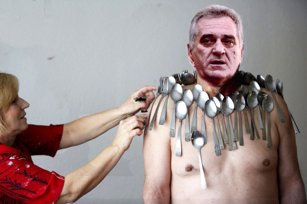 Muhibija Buljubasic, 56, stands as his wife Senija puts cutlery on his body in Srebrenik