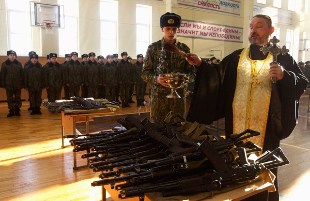 Image: Orthodox priest blesses rifles during a ceremony where new recruits receive their weapons at a military base of Belarussian Interior Ministry in Minsk