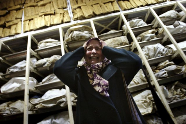 "Aida Civic, a Bosnian Muslim refugee woman from Srebrenica, screams as she enters a container with the remains of around 3,500 killed Bosnian Muslims, most of them from Srebrenica, in an identification centre of the Institute for missing persons in Tuzla in this December 10, 2002 file photo. Twenty years ago on July 11, 1995, towards the end of Bosnia's 1992-95 war, Bosnian Serb forces swept into the eastern Srebrenica enclave, a U.N.-designated ""safe haven"". There they took 8,000 Muslim men and boys and executed them in the days that followed, dumping their bodies into pits in the surrounding forests.     REUTERS/Damir Sagolj/"