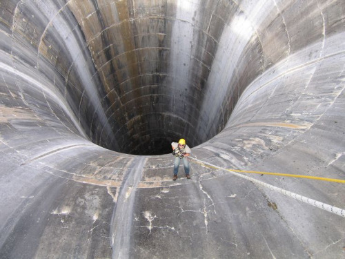 Brian Hollis rappels into Gibson Dam glory hole spillway. Photo by Joe Rohde
