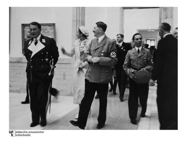 """Beim Eröffnungsrundgang - von links nach rechts: Hermann Göring, Gerdy Troost, Adolf Hitler, Joseph Goebbels, Adolf Ziegler (Rückenansicht, Organisator der Ausstellung). Aufnahmedatum: 19.07.1937 Aufnahmeort: München Systematik: Geschichte / Deutschland / 20. Jh. / NS-Zeit / Kunst und Kultur / Haus der Deutschen Kunst / Einweihung 1937 Hermann Göring, Gerdy Troost, Adolf Hitler, Joseph Goebbels, Adolf Ziegler (Rückenansicht, Organisator der Ausstellung, v.l.) machen am 19.07.1937 einen Rundgang in der gerade eröffneten """"Großen Deutschen Kunstausstellung"""" im Haus der Deutschen Kunst in München. Die Ausstellung fand zeitgleich zur Ausstellung """"Entartete Kunst"""" statt und zeigte die ideologisch zum Nationalsozialismus passenden Kunstwerke."""